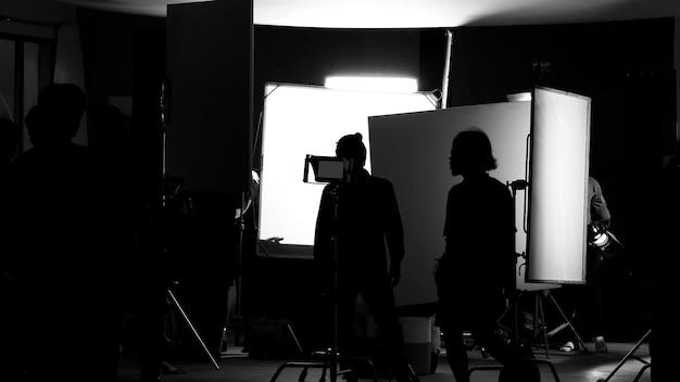 Drehstudio hinter den kulissen in silhouettenbildern, das team der filmcrew arbeitet für die dreharbeiten zu filmen