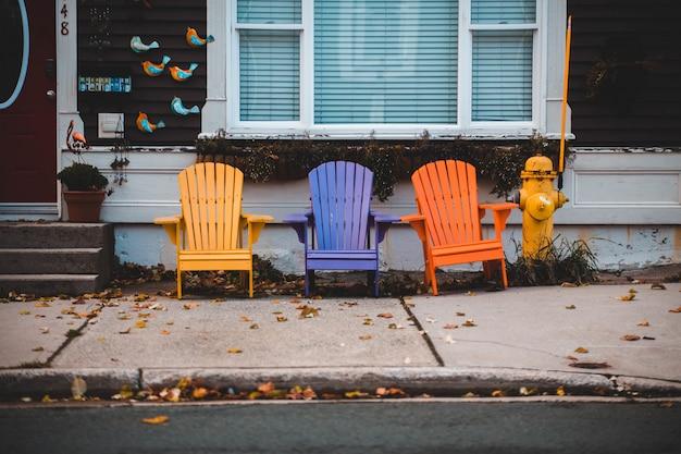 Drei adirondack-stühle in verschiedenen farben vor einem haus