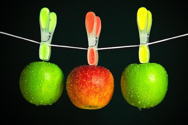 Drei äpfel in einer reihe auf schwarzem hintergrund