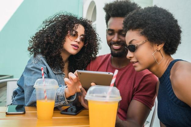 Drei afro-freunde mit digitalem tablet.