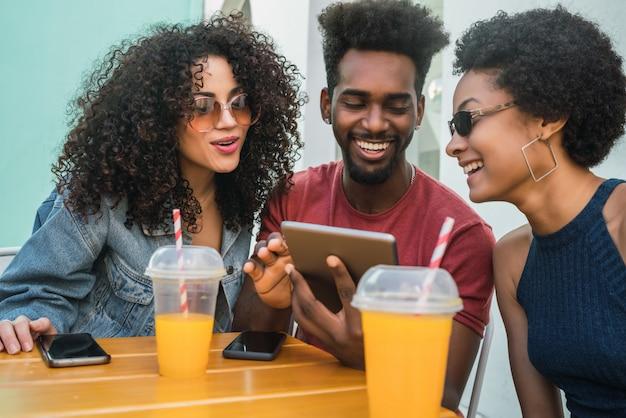 Drei afro-freunde mit digitalem tablet