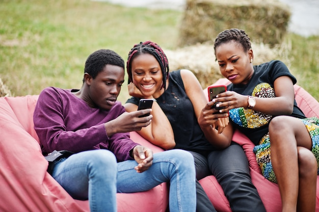 Drei afroamerikanische freunde entspannen sich, sitzen auf hockern und benutzen ihre telefone im freien.