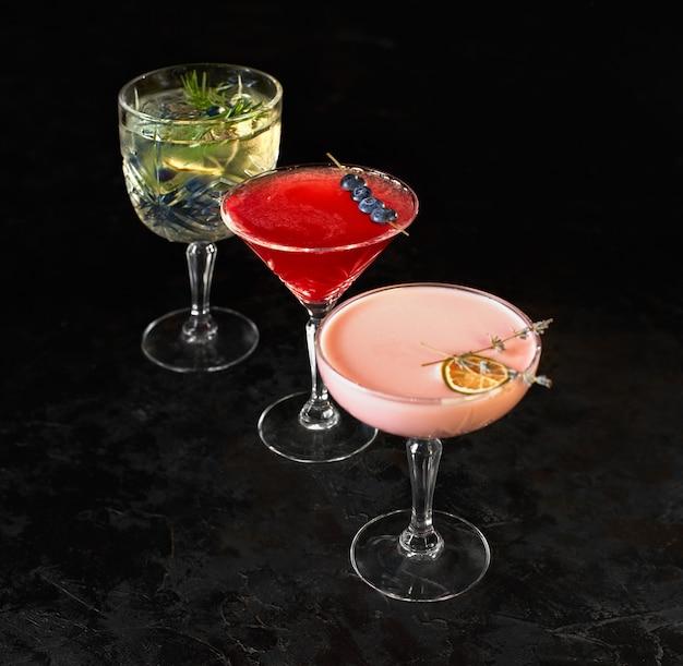 Drei alkoholische cocktails stehen auf einem schwarzen