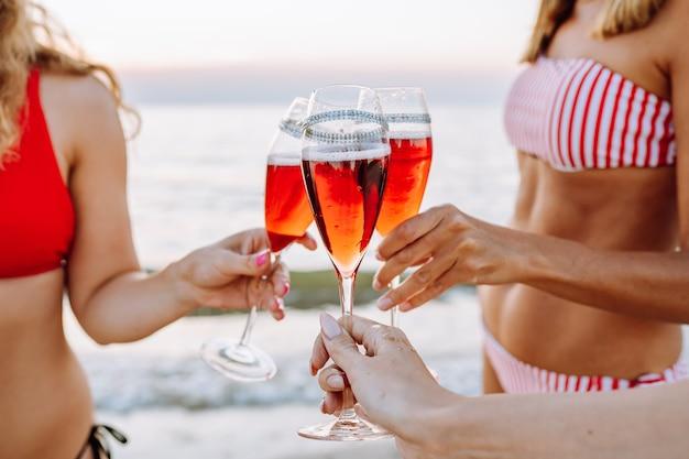 Drei aninymische frauen in bikinis, die gläser mit rotem champagner am strand bei sonnenuntergang blockieren