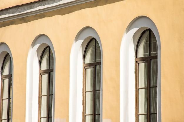 Drei antike bogenfenster in einem gelb-orange gebäude.