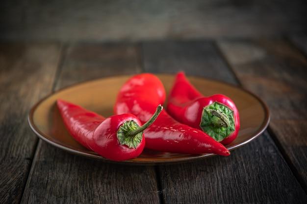 Drei appetitliche rote paprika auf einer keramikplatte auf einem küchentisch aus holz