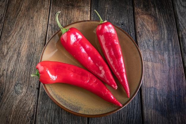 Drei appetitliche rote paprika in einer keramikplatte auf einem küchentisch aus holz