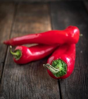 Drei appetitliche rote paprika liegen auf einem küchentisch aus holz