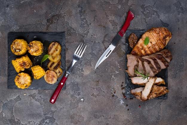 Drei arten von gegrilltem steak (huhn, schweinefleisch, rindfleisch) auf schieferplatte mit kräutern