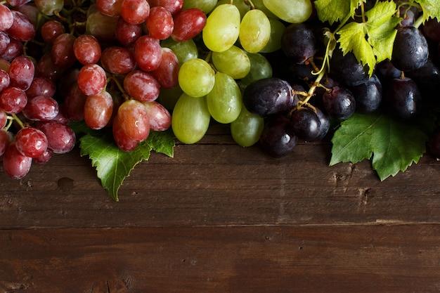 Drei arten von trauben auf einer holzoberfläche