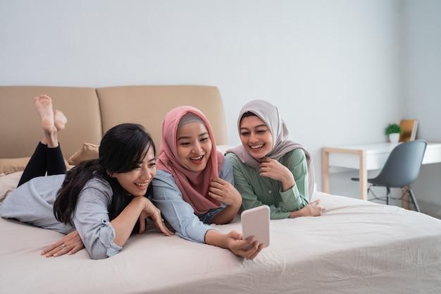 Drei asiatische frauen, die im bett liegen, während sie videoanrufe mit einem smartphone machen
