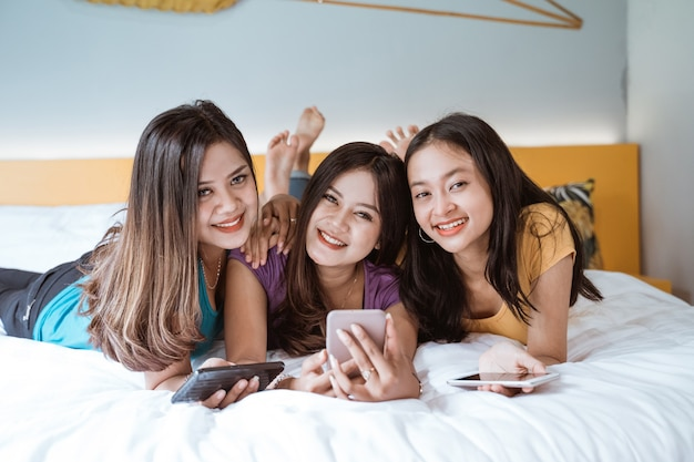 Drei asiatische freundinnen, die zusammen hängen und videoanruf machen