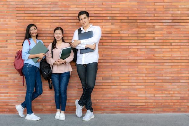 Drei asiatische lächelnde studenten, die buch und laptop halten, die auf backsteinmauer im campus aufwerfen.
