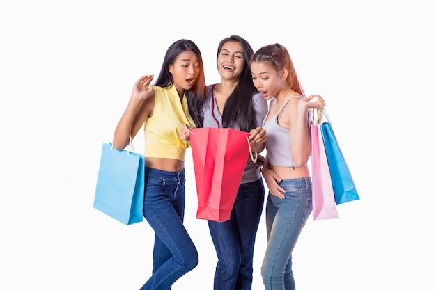 Drei asiatische mädchen, die einkaufstaschen halten und stehen zusammen beim kaufen abgesetzt