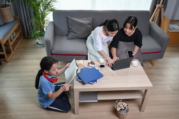 Drei asiatische mädchen sitzen in einem komfortablen zuhause und genießen ein gemeinsames freizeitwochenende