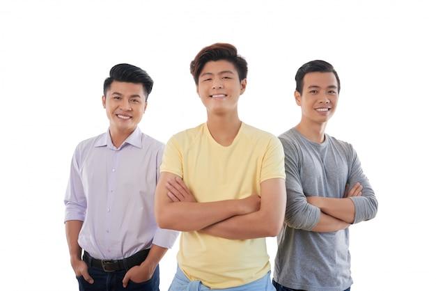 Drei asiatische männliche stehende und lächelnde freunde