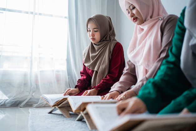 Drei asiatische mosleminnen lesen und lernen gemeinsam das heilige buch des al-quran