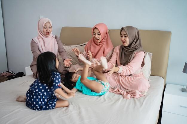 Drei asiatische mütter spielen gerne mit ihrer tochter im schlafzimmer
