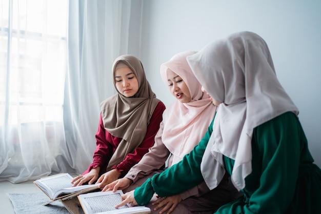 Drei asiatische muslimische frauen lesen und lernen gemeinsam das heilige buch des al-quran