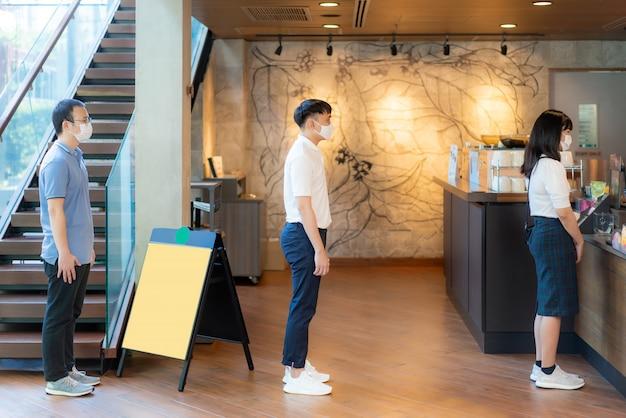 Drei asiatische personen, die eine maske tragen und einen abstand von 6 fuß zu anderen personen haben, halten abstand vor covid-19-viren und personen, die sich im kaffeecafé wegen des infektionsrisikos sozial distanzieren.