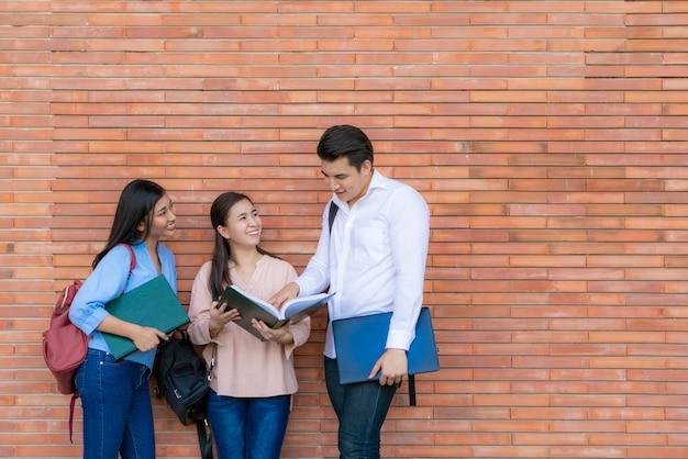 Drei asiatische studenten diskutieren über prüfungsvorbereitung, präsentation, studium, studium zur prüfungsvorbereitung an der universität.