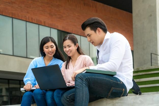 Drei asiatische studenten diskutieren über prüfungsvorbereitung, präsentation, studium und studienvorbereitung mit laptop an der universität.