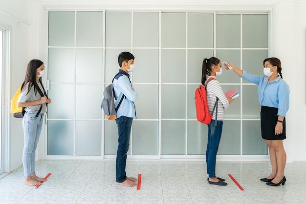 Drei asiatische studenten tragen maske, während lehrer thermometer-temperatur-screening-studenten verwenden