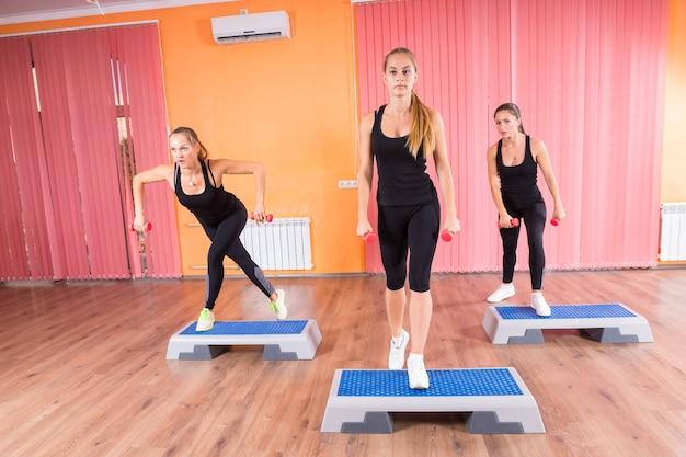 Drei athletische frauen in der trainingsklasse, die an kleinen hanteln und fitnessplattformen im fitnessstudio arbeiten.