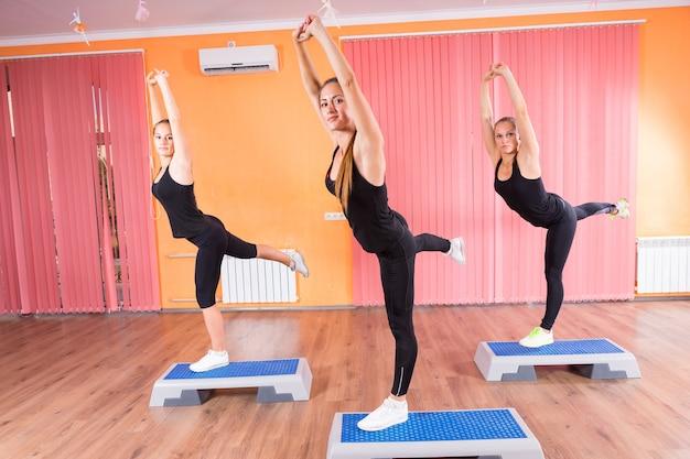 Drei athletische mädchen, die sich auf fitnessplattformen im fitnessstudio dehnen und balancieren und in die kamera schauen.