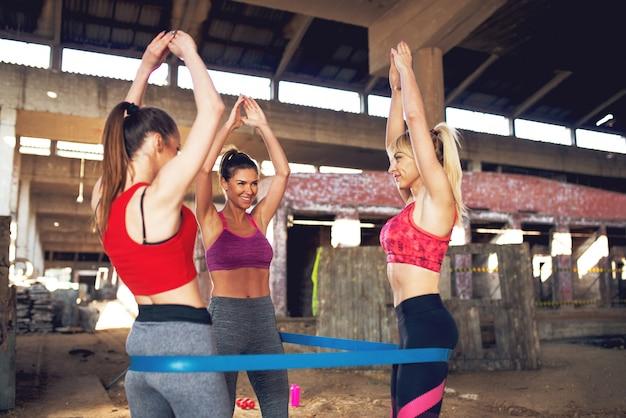 Drei attraktive formmädchen trainieren mit dem gummiband.
