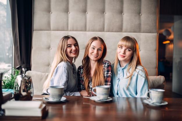 Drei attraktive freundinnen, die im café zu mittag essen. freundinnen sitzen im restaurant und trinken kaffee, klatsch treffen