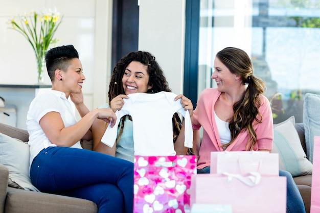 Drei auf dem sofa sitzende und beim betrachten von babys kleidung lächelnde frauen