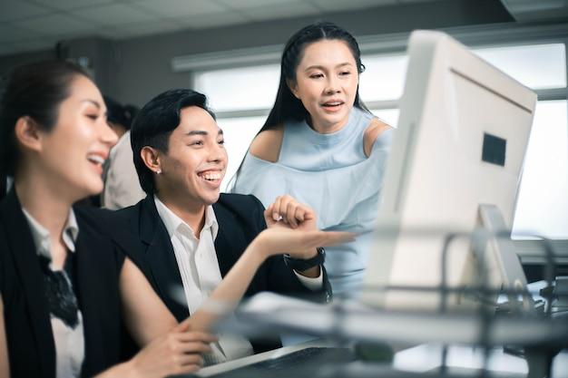 Drei aufgeregte mitarbeiter lesen online gute nachrichten auf einem computer-desktop im büro