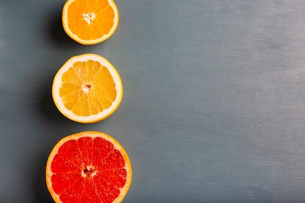 Drei ausgerichtete zitrusfrüchte auf tabelle mit kopieraum