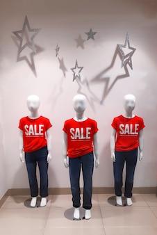 Drei baby-schaufensterpuppen in einem schaufenster mit roten t-shirts mit der aufschrift sale Premium Fotos