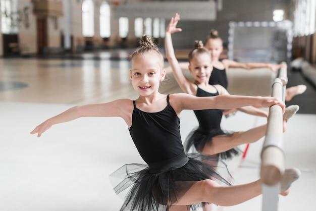 Drei ballerinamädchen im schwarzen ballettröckchen, das ihre beine auf stange ausdehnt