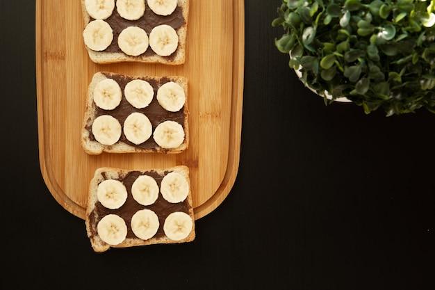 Drei bananenweißbrot-toasts verbreiteten mit schokolade