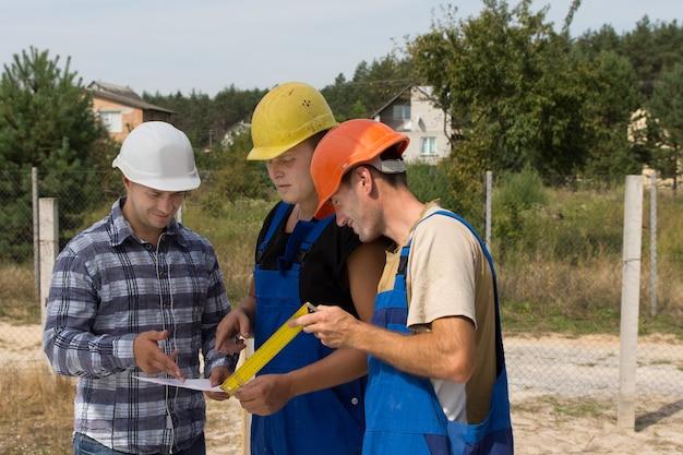 Drei bauarbeiter in ihren bauarbeiterhelmen stehen in einer gruppe und diskutieren auf einer baustelle papierkram, während sie versuchen, gemeinsam ein problem zu lösen