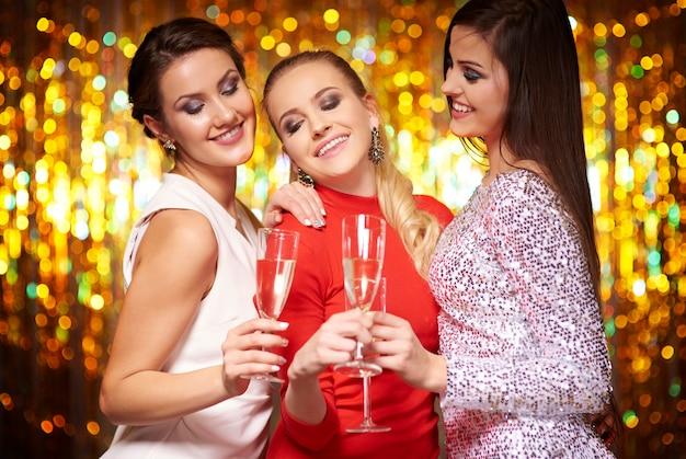 Drei beste freunde mit einem glas champagner