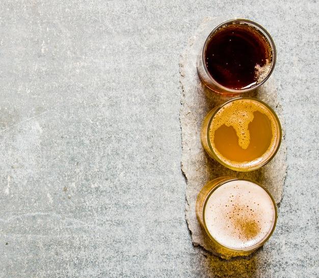 Drei biere auf einem steinsockel