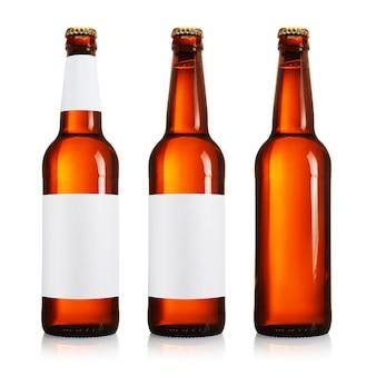 Drei bierflaschen mit langem hals und leerem etikett, braune farbe, isoliert auf weißem hintergrund.