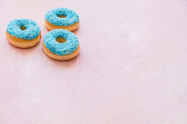 Drei blaue donuts auf rosa hintergrund