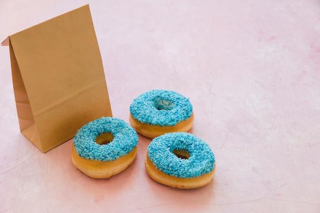 Drei blaue donuts mit paket auf rosa hintergrund