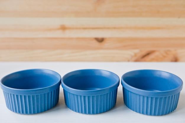Drei blaue keramikboxenteller und geschirr zum servieren eines festlichen tisches