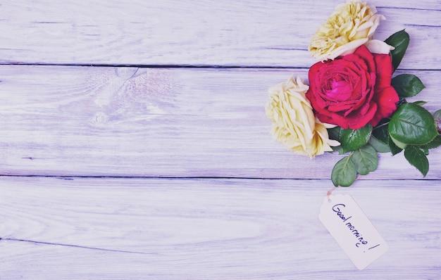 Drei blühende rosen auf einem weißen hölzernen hintergrund
