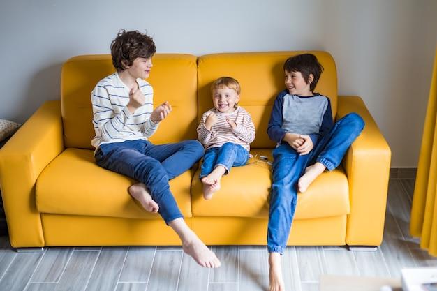 Drei brüder unterschiedlichen alters spielen und lachen auf einem gelben sofa