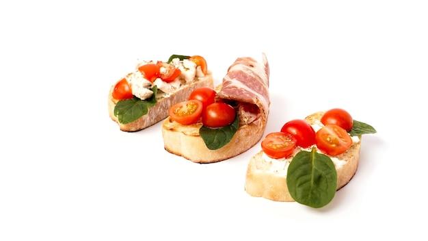 Drei bruschetta auf einem ciabatta auf einem weißen teller. italienische vorspeise auf einem isolierten hintergrund. set mit tomaten und speck