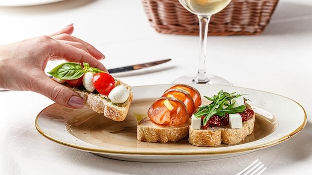 Drei bruschettas auf einem weißen teller mit käse, kirschtomaten, basilikum, verlust, sonnengetrockneten tomaten