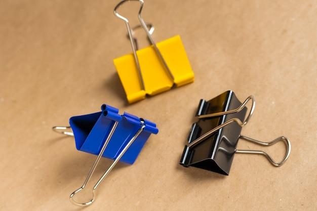 Drei büroklammern, blau, gelb und schwarz auf braunem grund. nahaufnahme. hintergrund, bastelpapier
