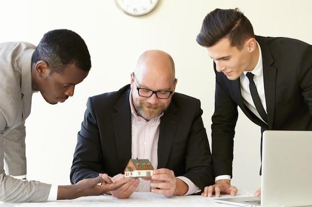 Drei büromänner schätzen das modell eines zukünftigen reihenhauses. kaukasischer ingenieur in gläsern, die miniatur halten und lächeln. andere kollegen in anzügen schauen sich mit interesse ein winziges haus an.